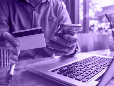 homem com celular e cartão nas mãos